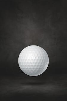 Balle de golf blanche isolée sur fond noir de studio.