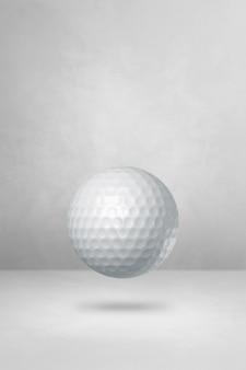 Balle de golf blanche isolée sur fond de studio vide.