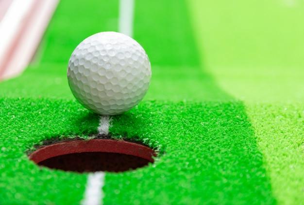 Balle de golf sur le bord de la coupe, concept d'objectif