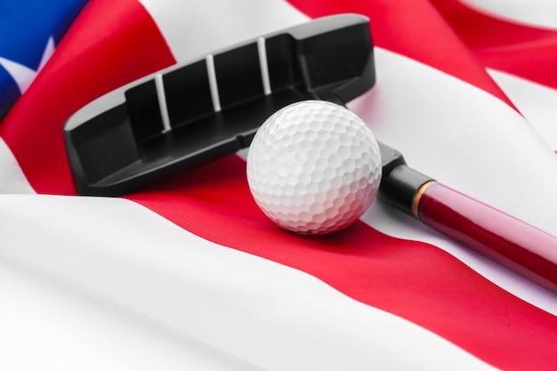 Balle de golf et club sur drapeau américain.