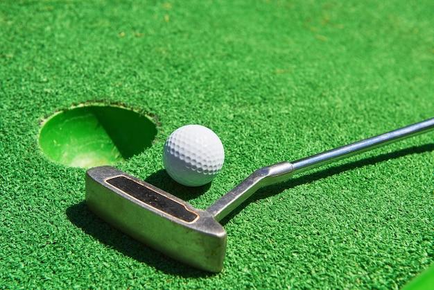 Balle de golf et club de golf sur gazon artificiel.