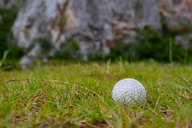 Balle de golf sur l'herbe près de la montagne