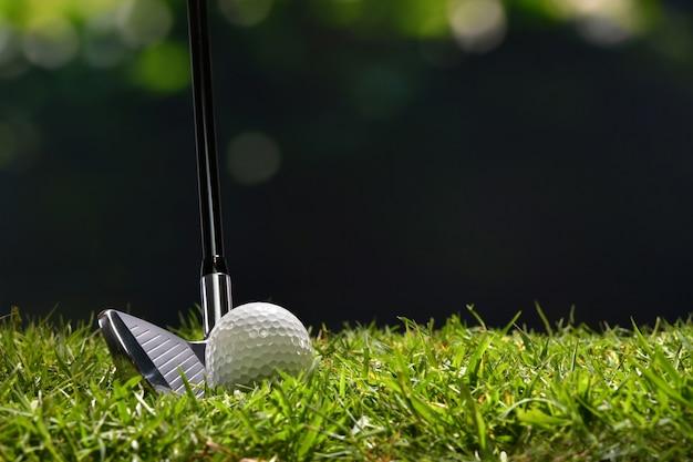 Balle de golf sur l'herbe verte prête à être frappée sur fond de parcours de golf