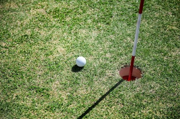 Balle de golf près du trou sur le terrain d'herbe verte.