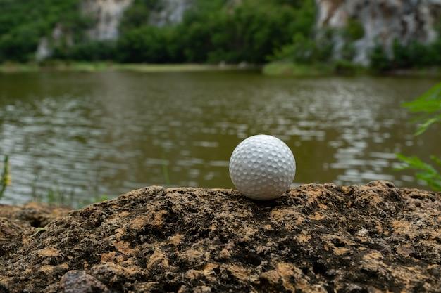 Balle de golf sur le rocher près du petit lac