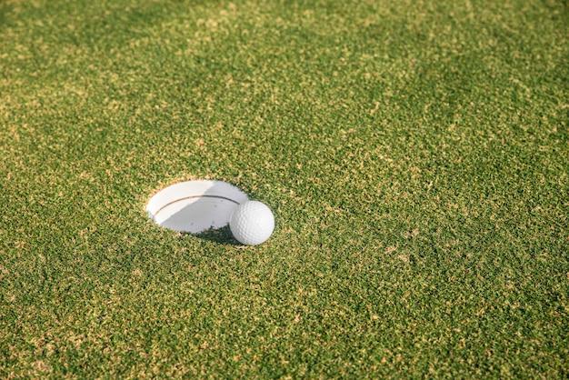 La balle de golf se trouve au bord du trou sur le green. concept de sport de golf