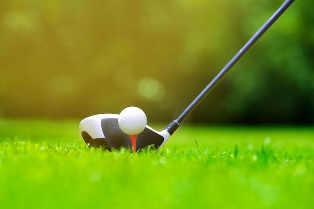 Balle de golf sur tee en face du conducteur sur un terrain vert gazon d'or, le conducteur positionné prêt à frapper la balle