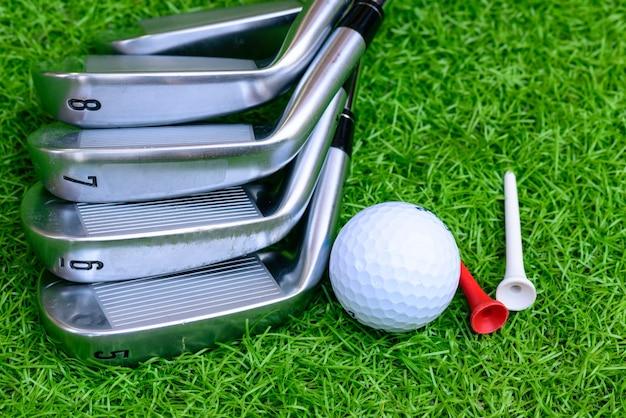 Balle de golf et tee sur fond de gaz vert