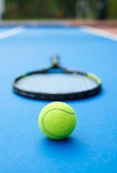 La balle jaune est posée sur un tapis de tennis bleu avec une raquette professionnelle.