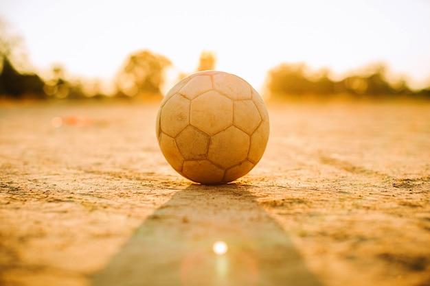 Une balle pour le football de football de rue sous la lumière du soleil couchant