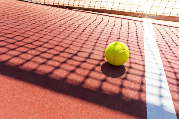 Balle de tennis sur un court de tennis avec filet