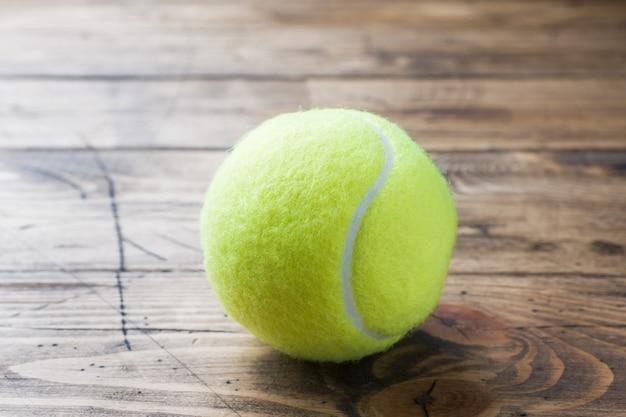 Balle de tennis sur fond de bois, concept et idée de sport, style rustique.