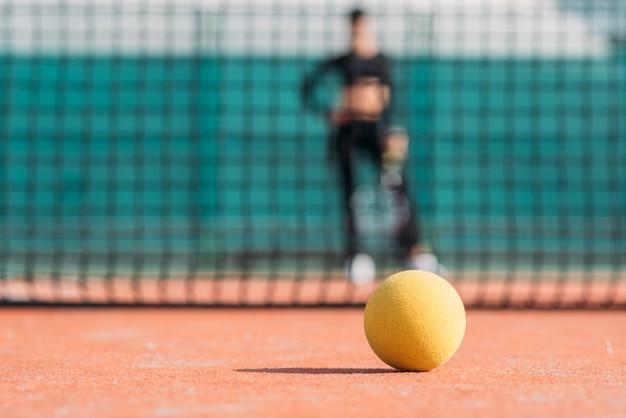 Balle de tennis gros plan sur un court de tennis avec fille sur fond