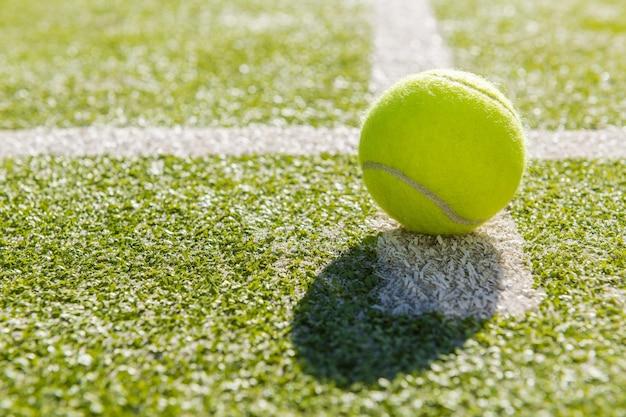 Balle de tennis jaune en cour sur gazon artificiel