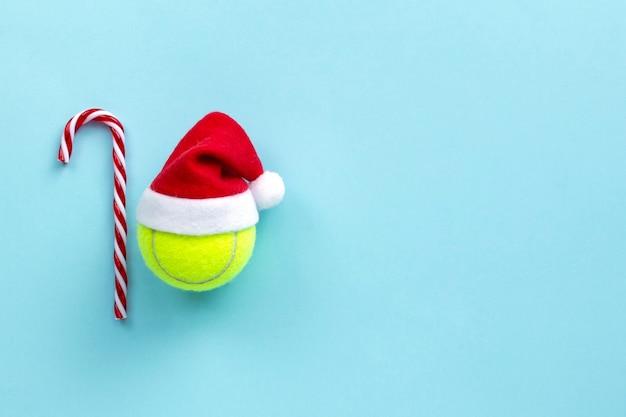 Balle de tennis jaune smiley en bonnet de noel, décoration de noël, concept de sport de tennis