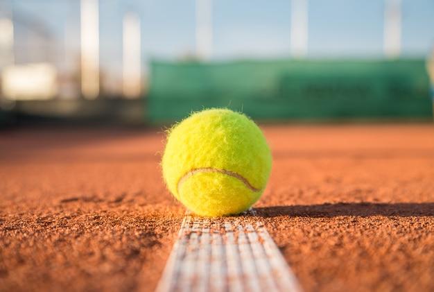 Balle de tennis se trouvant sur une ligne blanche sur un court de tennis par une journée ensoleillée.