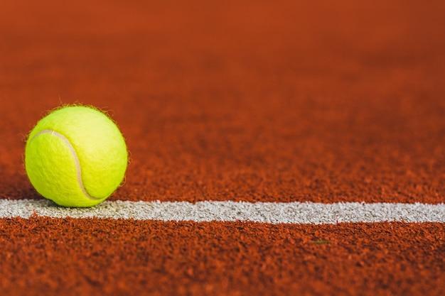 Balle de tennis sur le terrain en arrière-plan