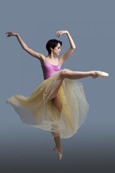 Ballerina danse en studio sur gris