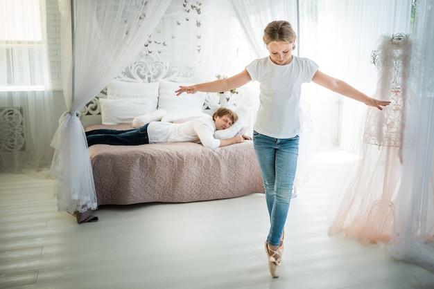 Ballerine adolescente non identifiée ficelle sur le sol devant un père fatigué assis sur le lit. le concept d'enfants hyperactifs et exigeants en attention