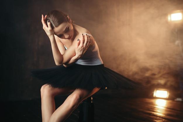 Ballerine assise sur une banquette noire sur la scène du théâtre. danseur de ballet d'élégance pose en classe
