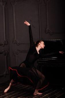 Ballerine en body foncé, en robe en studio intérieur sombre.