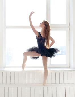 Ballerine classique femme en robe noire pratiquant pour le cygne noir