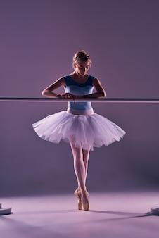 Ballerine classique posant à la barre de ballet