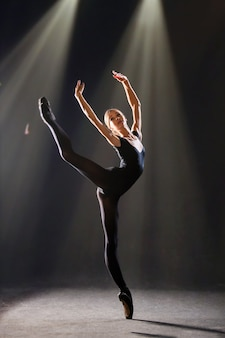 Ballerine en costume moulant danse sur fond noir sur des pointes, la silhouette est illuminée par des sources de couleur.