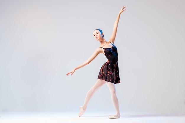 Ballerine dans une robe légère danse sur un mur blanc