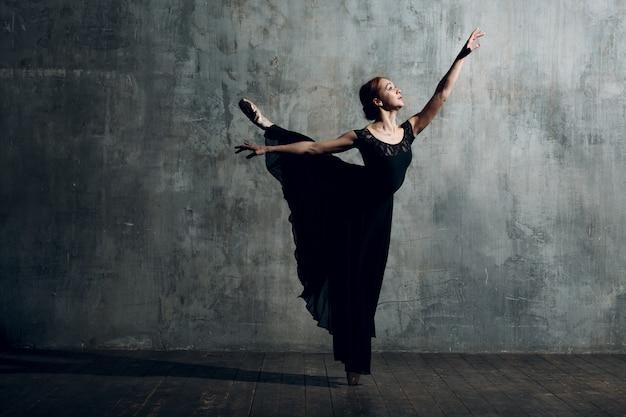 Ballerine femelle. belle jeune femme danseuse de ballet, vêtue d'une tenue professionnelle, de pointes et d'une robe noire.