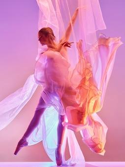 Ballerine. jeune danseuse de ballet féminine gracieuse dansant sur studio rose. beauté du ballet classique.