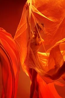 Ballerine. jeune danseuse de ballet féminine gracieuse dansant sur studio rouge. beauté du ballet classique.