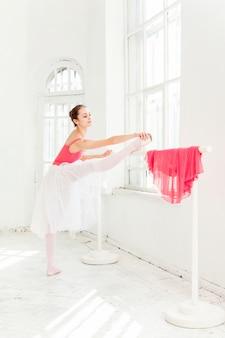 Ballerine posant en chaussons au pavillon en bois blanc