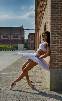 Ballerine pose sur le mur avec tutu