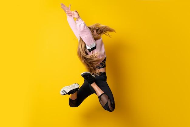 Ballerine urbaine dansant sur jaune isolé et sautant