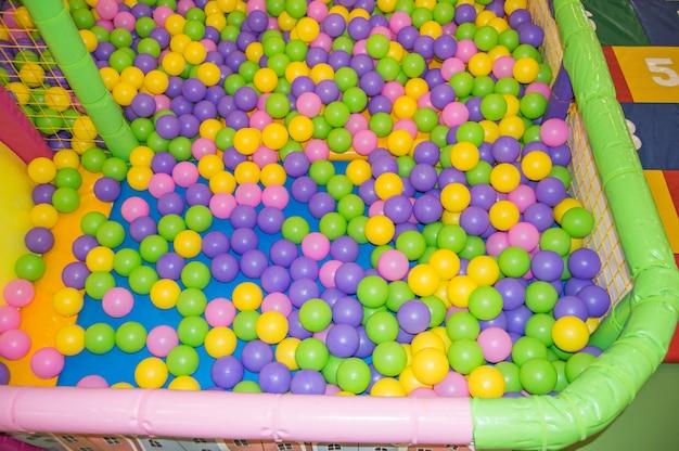 Balles multicolores en plastique colorées sur l'aire de jeux, piscine avec balles pour le développement des enfants et jeux.