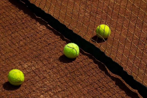 Balles de tennis et fragment de filet de court de tennis jeux et loisirs de plein air mise au point sélective