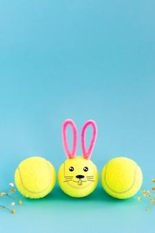 Balles de tennis jaunes avec oreilles de lapin et visage de dessin sur fond bleu avec espace de copie