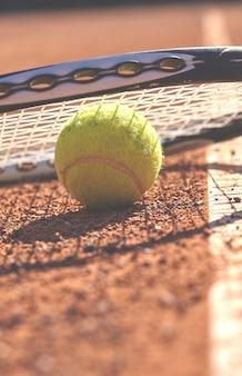 Balles de tennis et raquette sur terre battue
