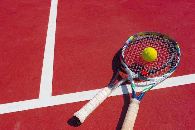Balles de tennis et raquettes sur le terrain