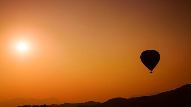 Ballon à air chaud silhouette sur les montagnes dans le ciel coucher de soleil
