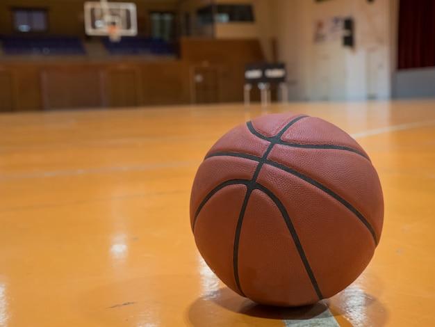 Ballon de basket-ball sur le terrain avec ligne de lancer franc, panier flou en arrière-plan.