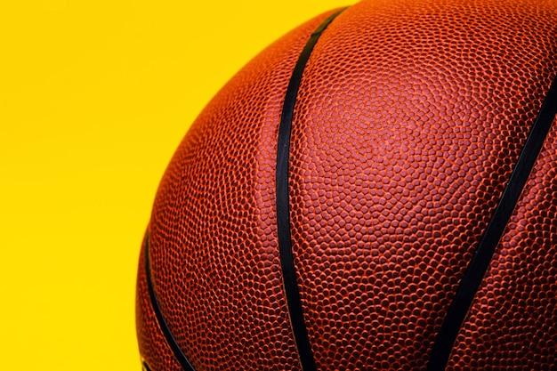 Ballon de basket sur espace jaune.