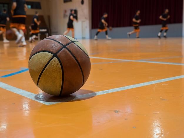 Ballon de basket sur le terrain avec ligne de lancer franc, joueurs flous
