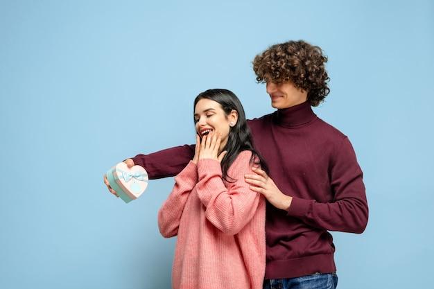Ballon coeur, embrassant. beau couple amoureux sur fond bleu studio. saint valentin, amour, relation et concept d'émotions humaines. copyspace. jeune homme et femme ont l'air heureux ensemble.