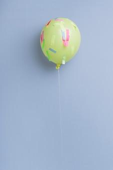 Ballon avec des confettis sur fond bleu