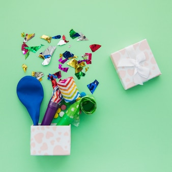 Ballon dégonflé; souffleurs de corne de parti et confettis dans la boîte ouverte sur fond vert