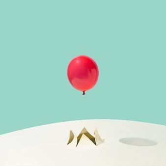 Ballon de fête d'été rouge volant d'une fissure sur fond jaune et bleu. concept abstrait minimal. disposition carrée avec espace de copie.