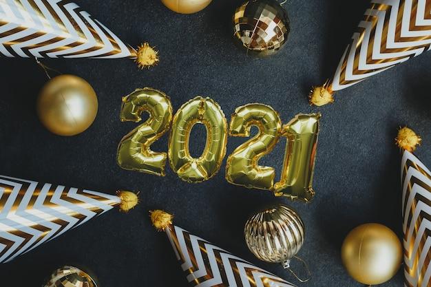 Ballon de fête en métal doré avec chiffres, boules d'or et casquettes de fête, sur fond noir