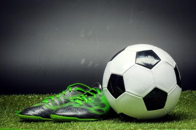 Ballon de foot et crampons sur le terrain de football